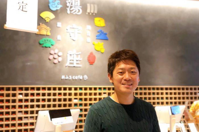 湯守座の店名ロゴを背景に立つ宮本さん